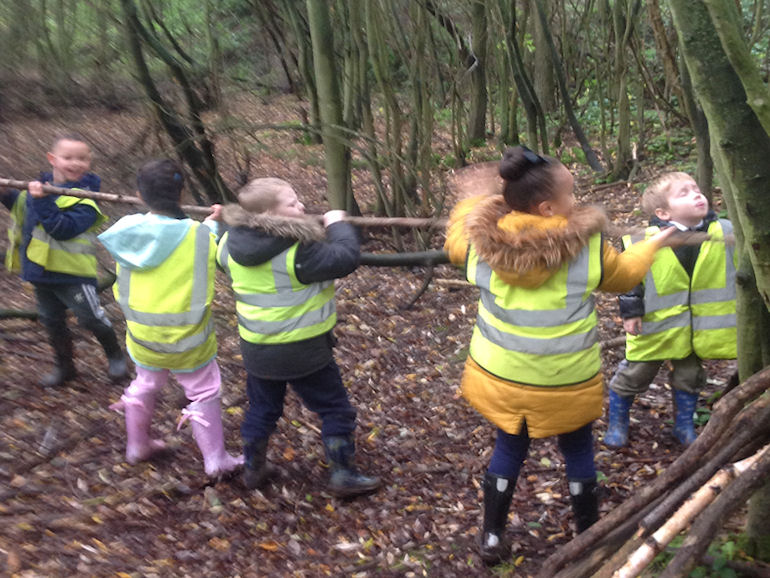 Children building a shelter in Forest School