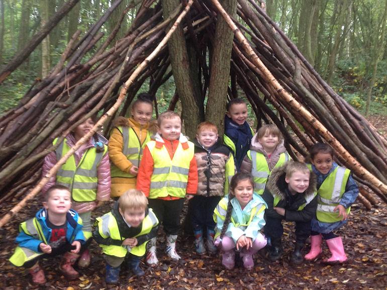 Children under a wooden shelter